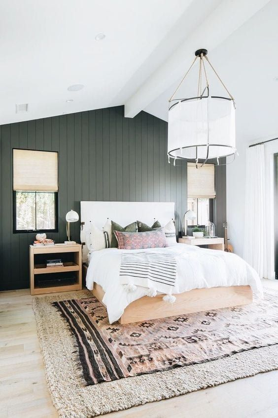 a stylish bedroom with a graphite grey planked accent wall, a neutral bed and printed bedding, matching nightstands and a pendant lamp