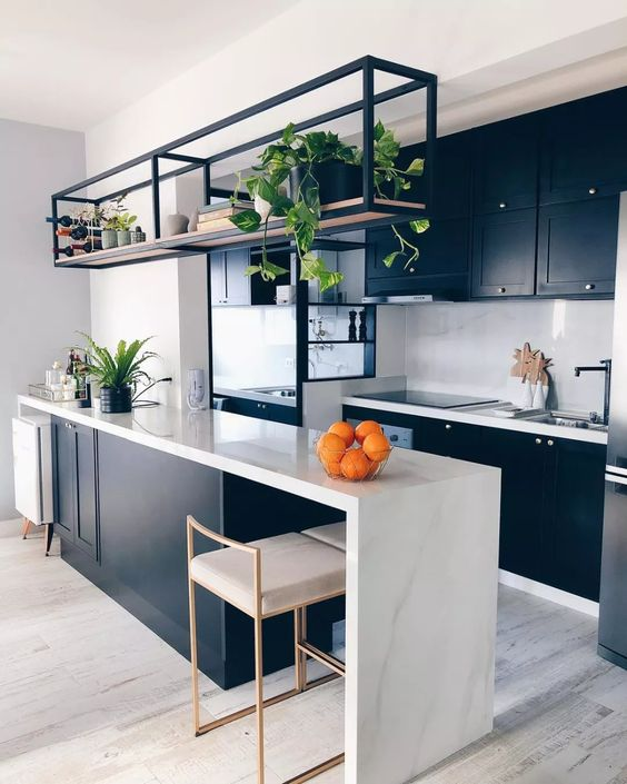 a stylish contemporary kitchen with black cabinetry, alarge kitchen island with a waterfall countertop, a black metal shelf and black fixtures