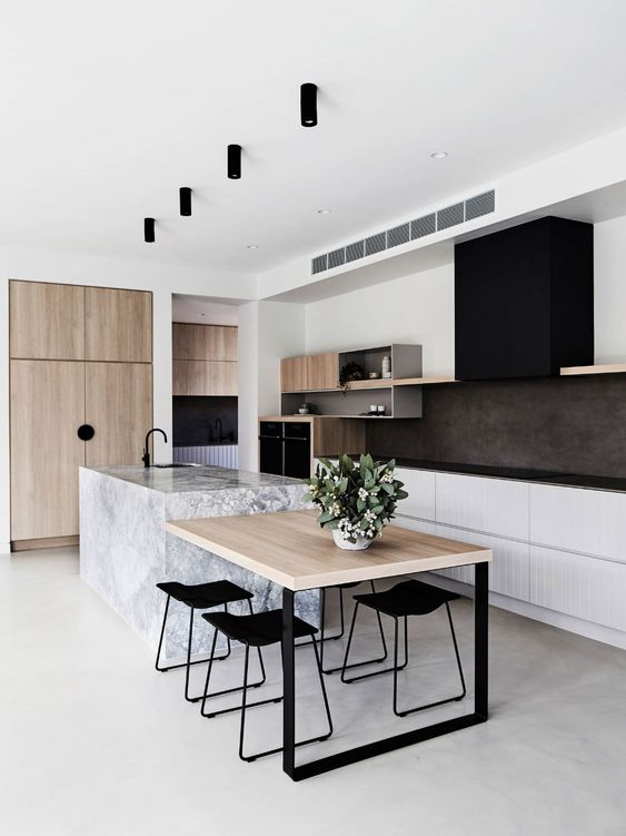 a stylish contemporary kitchen with white lower cabinets, open storage shelves, a black hood, black countertops, light stained wood and a stone kitchen island