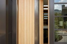 a stylish light-stained and metal pivot entrance door is a lovely solution for a modern home and adds chic to the porch