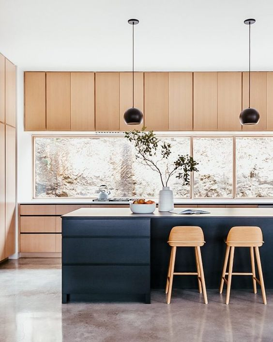 a stylish light stained kitchen with a large window backsplash, a navy kitchen island, black pendant lamps and tall stained stools is perfection