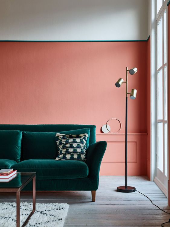 a stylish living room with a color block white and orange accent wall, a dark green velvet sofa, a floor lamp and a glass coffee table