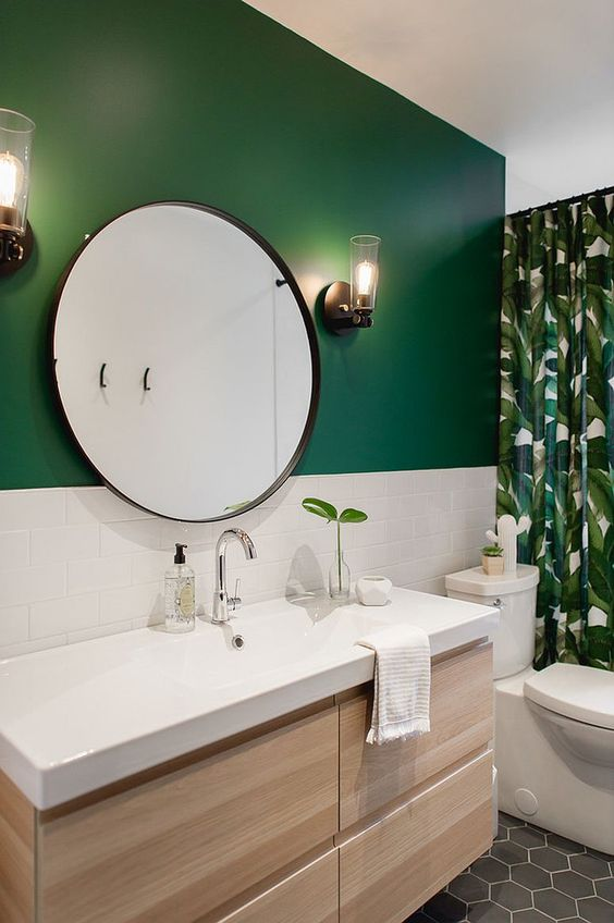 a stylish modern bathroom with a green accent wall, a floating light stained vanity, a round mirror and a tropical print curtain