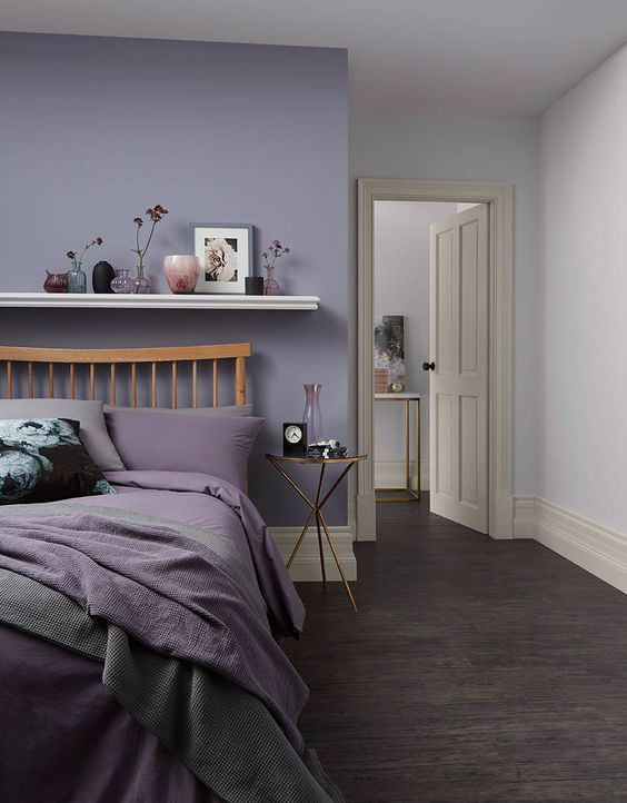 a stylish modern bedroom with a lilac accent wall, a wooden bed with lilac and grey bedding, a floating shelf with lovely decor
