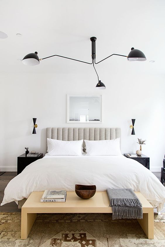 a stylish neutral bedroom with a grey upholstered bed, a wooden bench, dark matching nightstands and a black chandelier