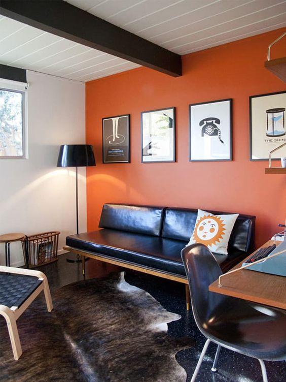 a stylish orange home office with a dark wooden beam, a black leather daybed, black chairs, a cool desk and layered rugs plus a gallery wall