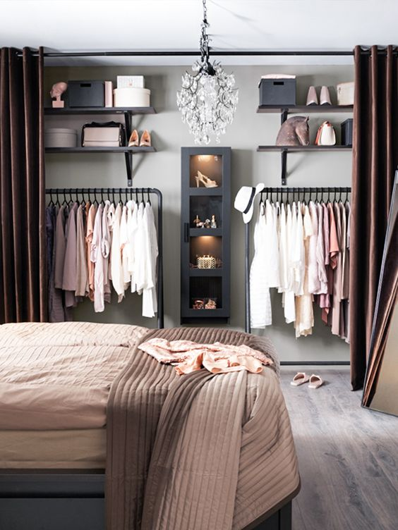 a stylish warm-colored modern bedroom with a large organized closet with chocolate brown curtains is a practical idea