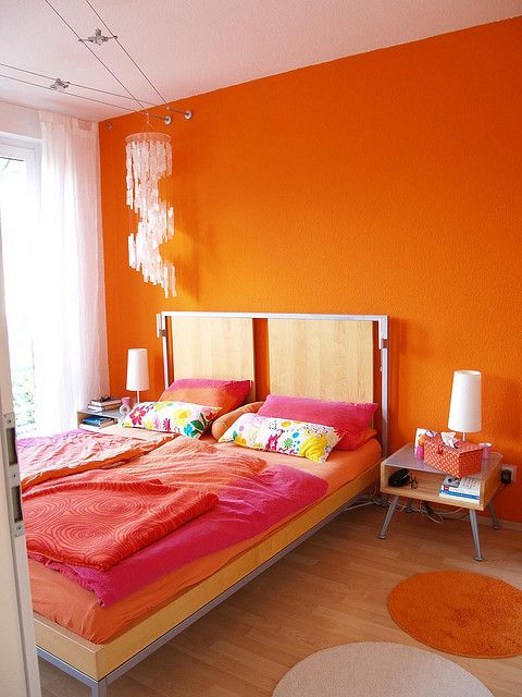 a super colorful bedroom with an orange accent wall, chic mid-century modern furniture, bold bedding, a crystal chandelier and bold rugs