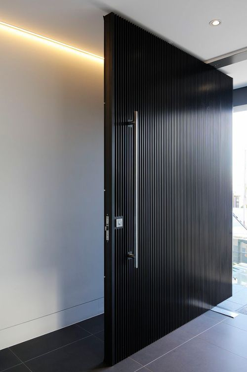 a super elegant black wooden slab door with a large metal handle is a cool and bold idea for a minimalist or conteporary home
