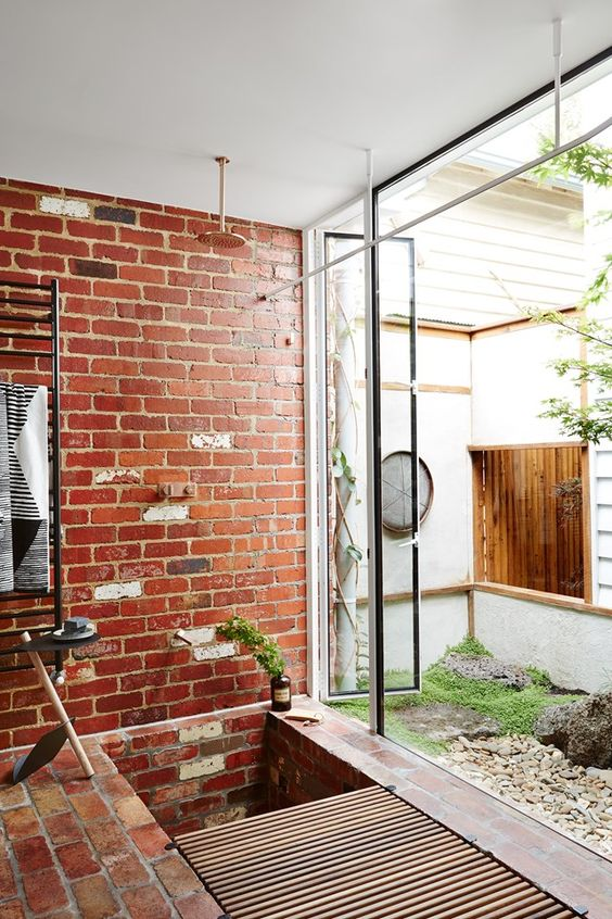 a sustainable bathroom with exposed brick walls and a floor, a wooden slab mat and metal framing is a cool space with style