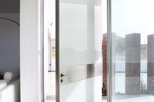 a unique frosted glass and metal pivot door is an ultra-modern and fresh solution is a bold statement for any space