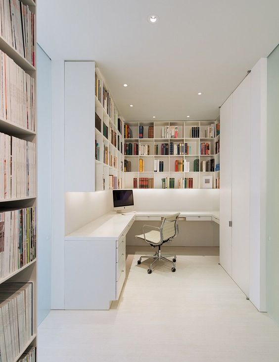 a very simple contemporary home office nook with lots of shelves for storage, a corner desk, a white chair and built-in lights
