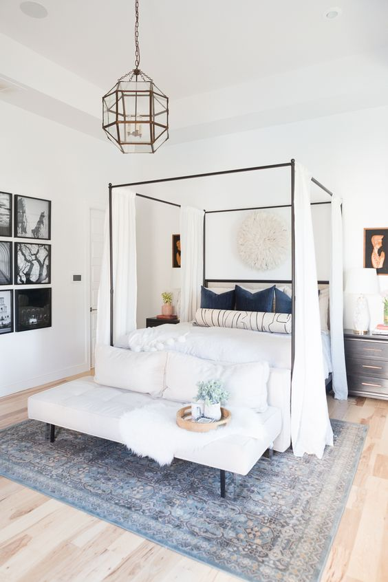 a welcoming bedroom in neutrals with a canopy bed and curtains, a grid gallery wall, black nightstands, an upholstered bench and pillows