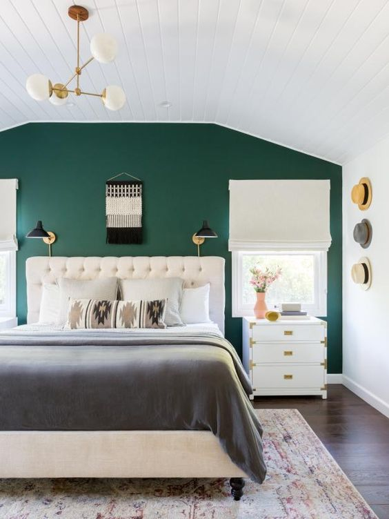 a welcoming boho bedroom with an emerald accent wall, a creamy upholstered bed, white nightstands, a macrame decoration and hats as decor
