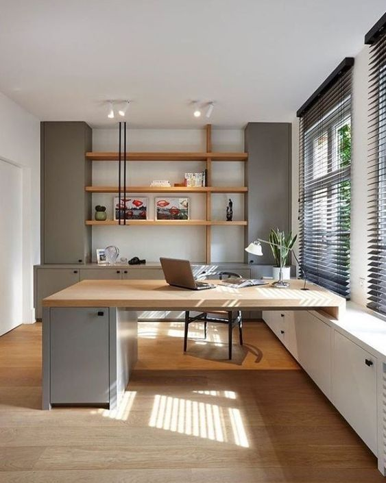 a welcoming contemporary home office with light grey storage units, stained shelves, a built-in matching desk and a black chair