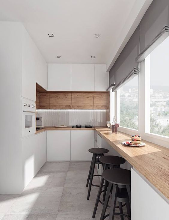 a welcoming contemporary kitchen with sleek white cabinets, a row of stained ones and a matching butcherblock countertop, a meal space by the window