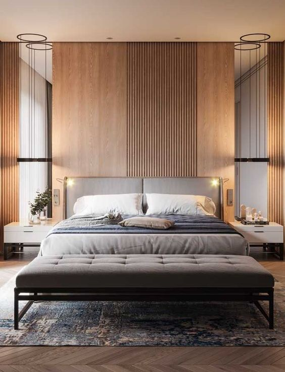 a welcoming contemporary living room with an accent wall, mirrors, an upholstered bed, a grey upholstered bench and cool lights