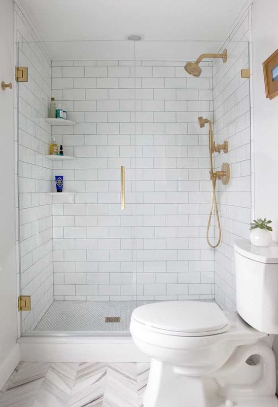 a white bathroom with subway and chevron tiles, gold fixtures and white appliances is a stylish idea that always works