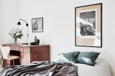 an airy and light bedroom with a bed and a vintage wooden desk in the corner plus some chic artworks is a lovely space