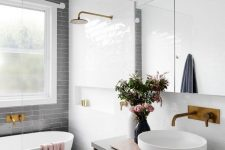 an airy contemporary bathroom with a grey subway tile accent wall, blue and white tiles on the floor, a floating vanity, brass fixtures and a window