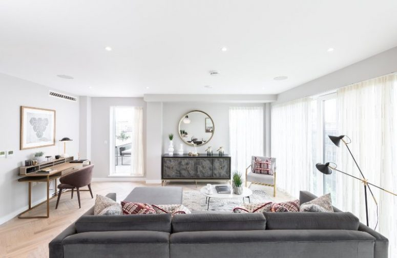 an airy contemporary living room with a refined credenza, a grey sectional, light grey chairs, a floor lamp and a vintage desk