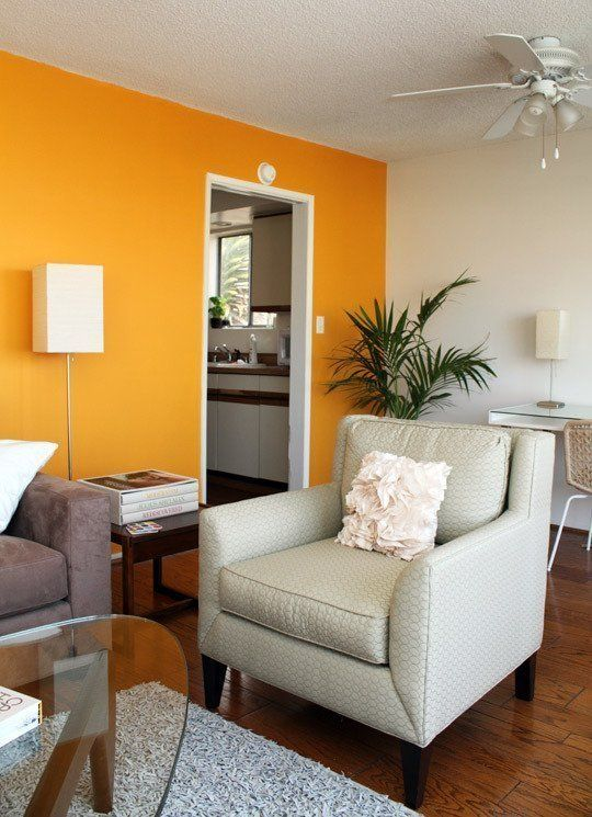 an elegant modern living room with a bright orange accent wall, a grey sofa and a neutral printed chair, a cool desk and a woven chair plus a glass table