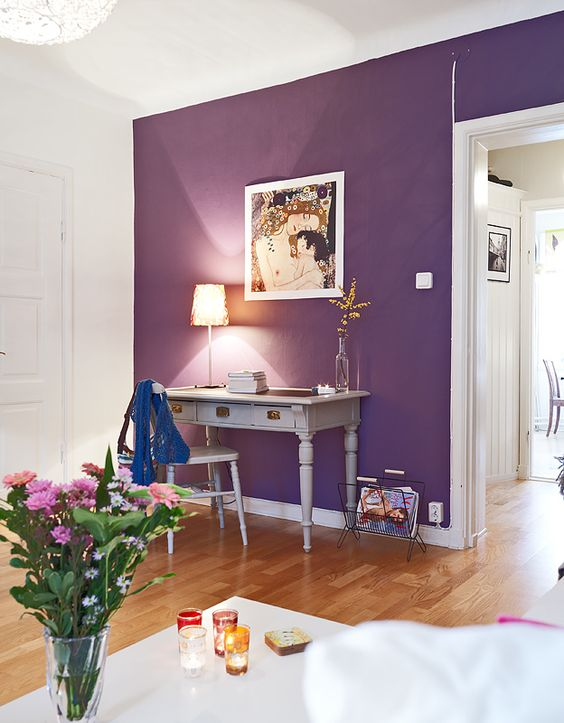 an elegant space with a purple accent wall, a vintage home office nook with grey furniture, bold blooms and white furniture