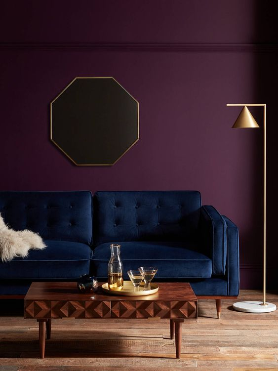 an exquisite living room with a deep purple accent wall, a navy sofa, a beautiful wooden coffee table and a gold floor lamp