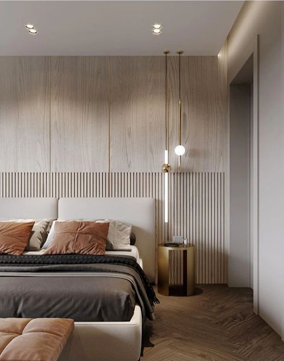 an inviting neutral contemporary bedroom with a planked accent wall, a neutral upohlstered bed, black and rust bedding, a pendant lamp and a leather bench