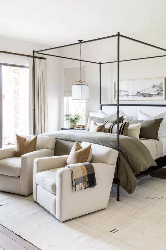 an inviting neutral modern bedroom with a canopy bed, muted and printed bedding, a pendant lamp, creamy chairs  and an artwork