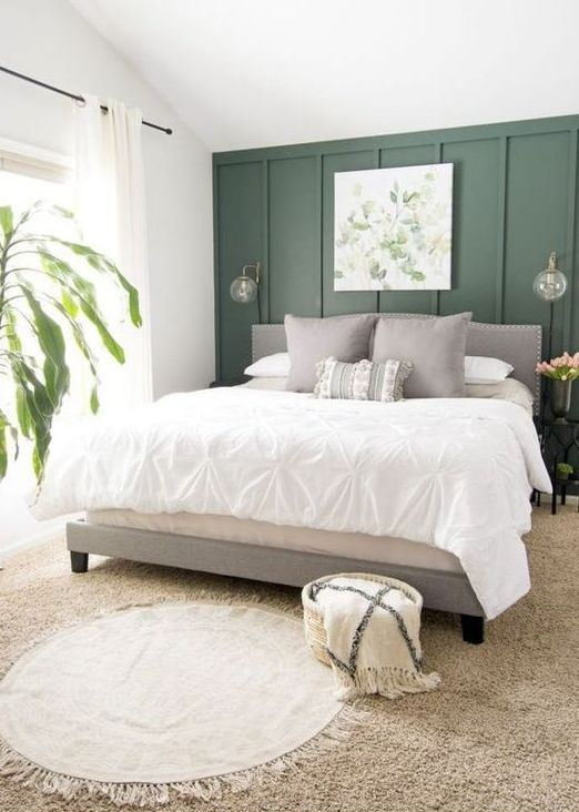 an organic bedorom with a green paneled accent wlal, a grey upholstered bed, neutral bedding, layered rugs and a botanical artwork and a potted plant