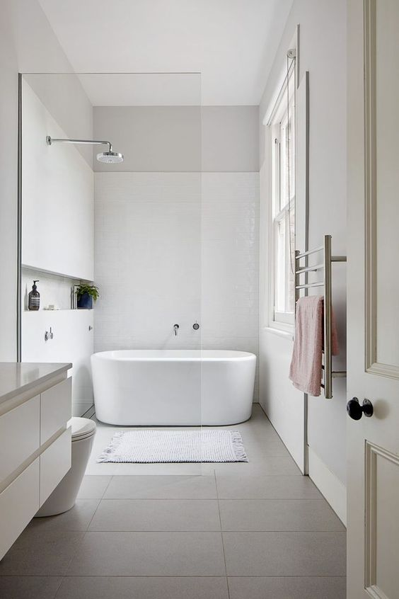 an ultra-minimalist bathroom with white and grey tiles, an oval tub, chrome fixtures and pastel textiles and a window for more light