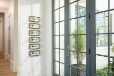 beautiful modern grey French doors and matching windows flood the entryway with light and make it look sophsiticated at the same time