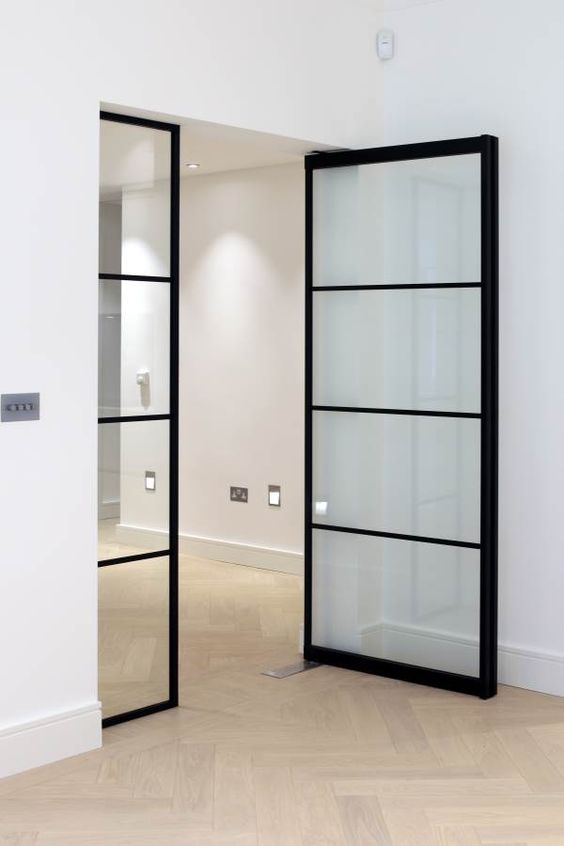 stylish black metal frame and glass pivoting doors are great for indoor use as they give a light feel to the interior and spearate the spaces