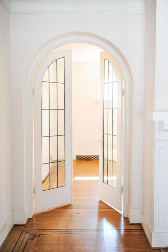 very chic and beautiful arched French doors with black frames and white base are an interesting and catchy solution for any space