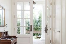 white French doors at the entrance are a very elegant and stylish idea that is timeless and can work for many decor styles