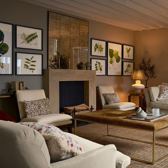 a chic taupe living room with a non-working fireplace, a botanical gallery wlal, neutral seating furniture, a metal and glass coffee table