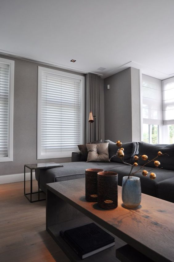 a contemporary taupe living room with a dark grey sofa, a wooden coffee table and a stone side table, a tan pillow and a copper lamp