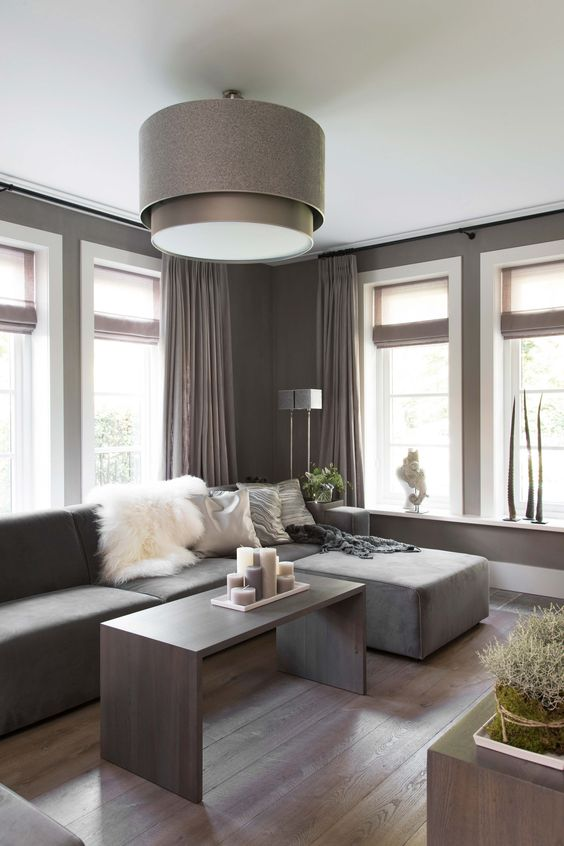 a lovely taupe contemporary living room with a matching low sofa, taupe curtains, a taupe coffee table with lots of candles and a taupe pendant lamp