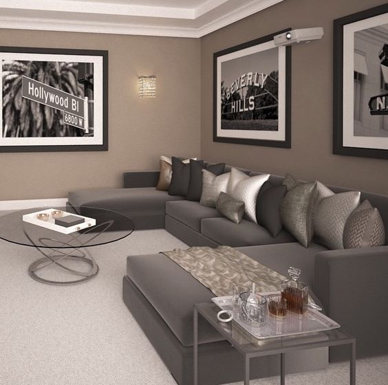 a refined taupe living room with a grey sectional, an arrangement of metallic pillows, a black and white gallery wall, glass coffee tables