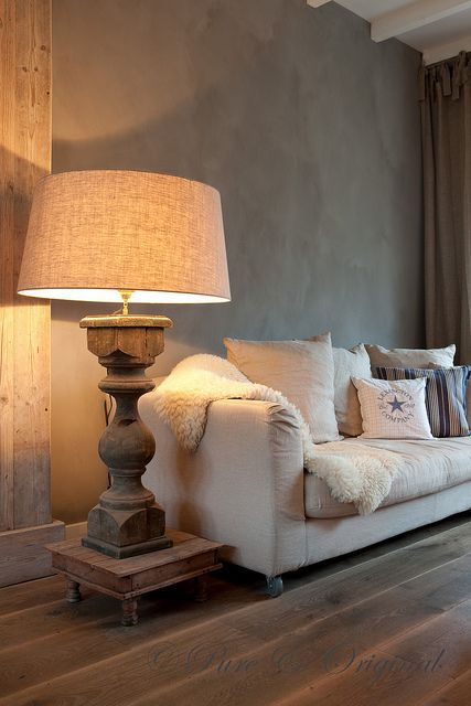 a refined taupe living room with rich stained floors, a creamy sofa, a wooden stand with an oversized lamp on a wooden carved stand