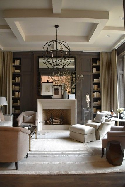 a sophisticated taupe living room with paneling, built-in bookshelves, a non-working fireplace, neutral seating furniture, a sphere pendant lamp and a large mirror