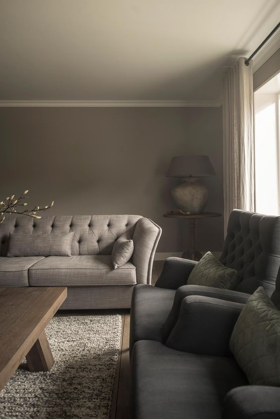 a taupe living room with a greige sofa, grey chairs, a printed rug, a wooden coffee table and a large table lamp