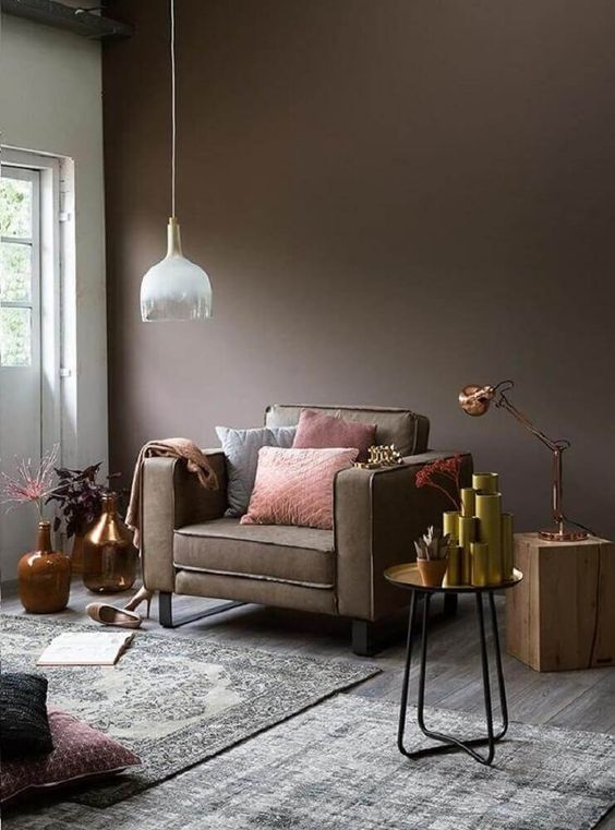 a taupe living room with a taupe chair, a tree stump and a metal side table, lots of vases, potted plants and layered rugs