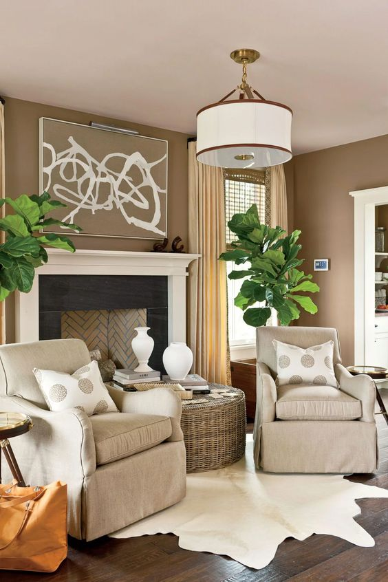 a welcoming taupe living room with a vintage-styled fireplace, tan chairs, a woven coffee table, statement potted plants and polka dot pillows
