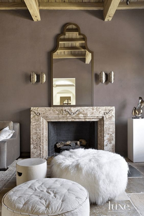 an exquisite taupe living room with a non-working fireplace, a refined mirror, metallic sconces, white ottomans and poufs and taupe furniture