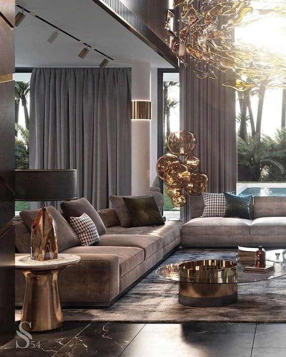 an exquisite taupe living room with taupe sofas and curtains, a brown rug, a glass and metal coffee table and a gorgeous chandelier