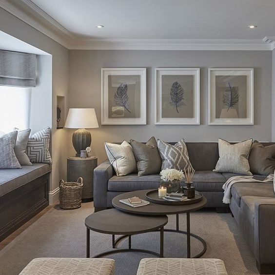 a cozy small grey living room with a windowsill daybed with printed pillows, a taupe sectional, a duo of brown round tables and a cool gallery wlal