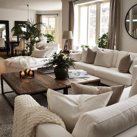 a grey living room with creamy sofas and a lounger, taupe and creamy pillows, taupe curtains, a duo of rich-stained coffee tables