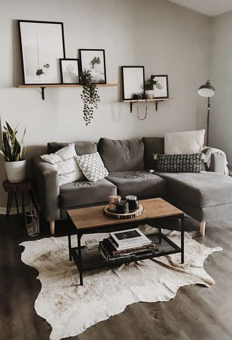 a light grey living room with a taupe sectional, a mini gallery wall, potted plants, an animal skin rug and a small coffee table